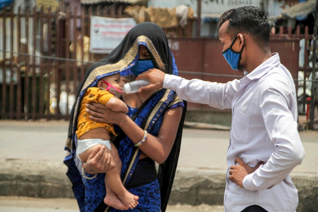 Mumbai: A migrant couple, travelling to Madhya Pradesh, feed their child as they arrive at Borivali station to board a train during the nationwide COVID-19 lockdown, in Mumbai, Monday, May 18, 2020. (PTI Photo)(PTI18-05-2020 000336B)