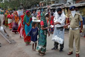 Slum dwellers in Ahmedabad receive free food packets during a 21-day nationwide lockdown [Amit Dave/Reuters]