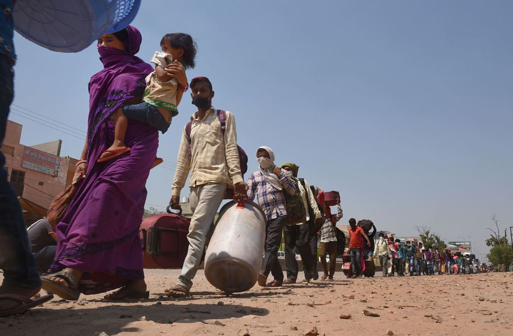 Dadri: Migrant workers wait in a queue while being lodged at a camp by the Uttar Pradesh government, during ongoing COVID-19 lockdown, at Dadri in Gautam Buddha Nagar district, Wednesday, May 20, 2020. (PTI Photo/Atul Yadav) (PTI20-05-2020_000214B)