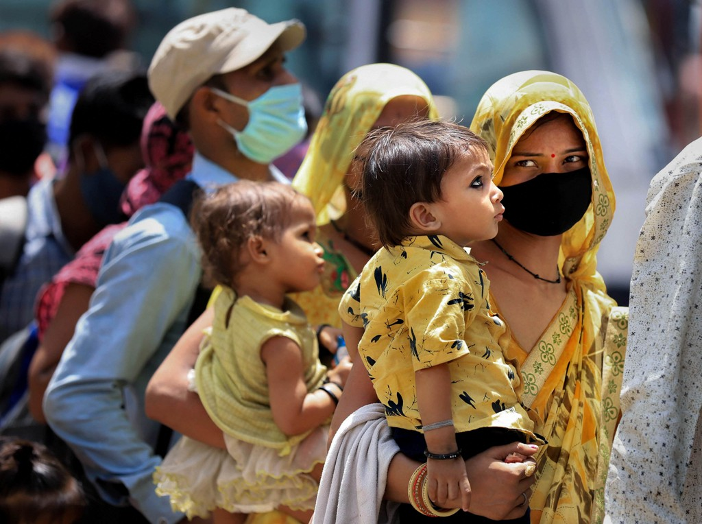 Prayagraj: Migrants wait to board buses to reach their native places after arriving via special train, during the ongoing COVID-19 lockdown, in Prayagraj, Tuesday, May 26, 2020. (PTI Photo) (PTI26-05-2020 000040B)