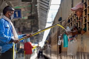 Jabalpur: Railway official provides drinking water from a distance to migrants travelling by a train to their native places, during the ongoing nationwide COVID-19 lockdown, at a railway station in Jabalpur, Wednesday, May 27, 2020. (PTI Photo) (PTI27-05-2020 000149B)(PTI27-05-2020 000198B)