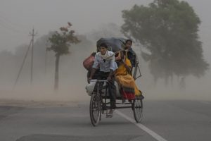 Prayagraj: A rickshaw puller ferrying passengers rides through a dust storm, in Prayagraj, Saturday, May 30, 2020. (PTI Photo)(PTI30-05-2020 000161B)