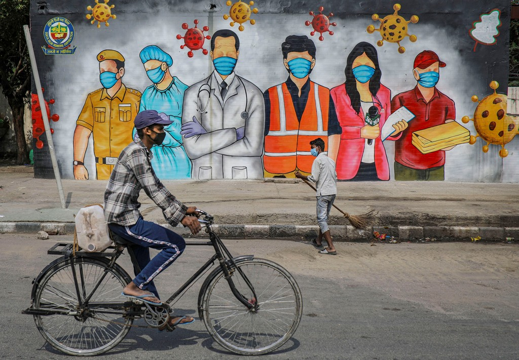 New Delhi: A cyclist rides past a mural that reads A Big Salute To Corona Warriors, during ongoing COVID-19 lockdown, in New Delhi, Sunday, May 31, 2020. (PTI Photo/Ravi Choudhary)(PTI31-05-2020 000132B)