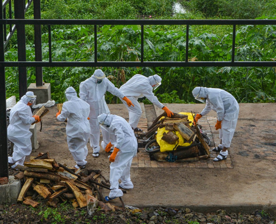 Karad: Municipal workers and family members wearing protective suits cremate the body of a person who died of COVID-19 at a crematorium, during the ongoing nationwide lockdown, in Karad, Friday, June 26, 2020. (PTI Photo)(PTI26-06-2020 000179B)