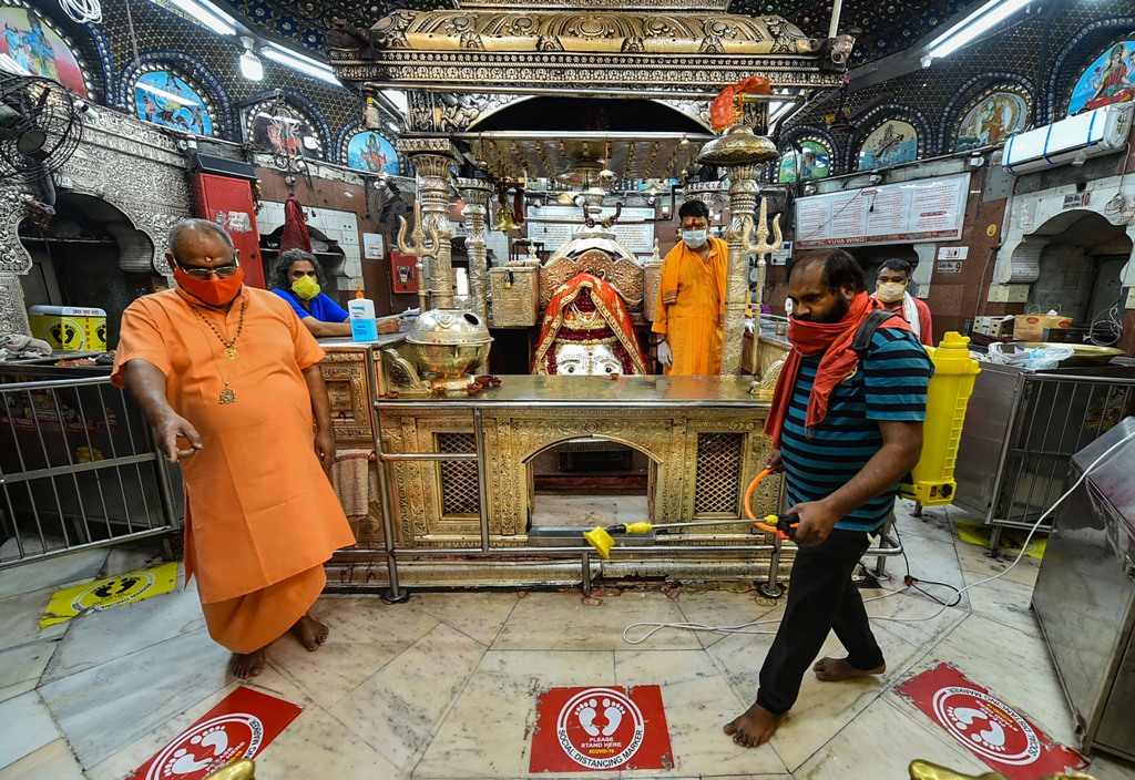 New Delhi: A worker sprays disinfectant inside Kalka Ji temple ahead of its re-opening for devotees, during the ongoing COVID-19 lockdown, in New Delhi, Sunday, June 7, 2020. (PTI Photo/Arun Sharma)(PTI07-06-2020 000050B)