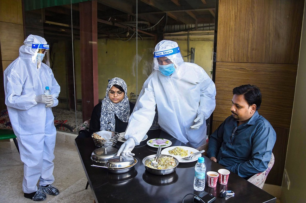 Patna: Waiters wearing PPE kits serve food to customers at a restaurant after the authorities permitted opening of eateries, during the ongoing COVID-19, lockdown, in Patna, Monday, June 8, 2020. (PTI Photo)(PTI08-06-2020 000167B)(PTI08-06-2020 000301B)