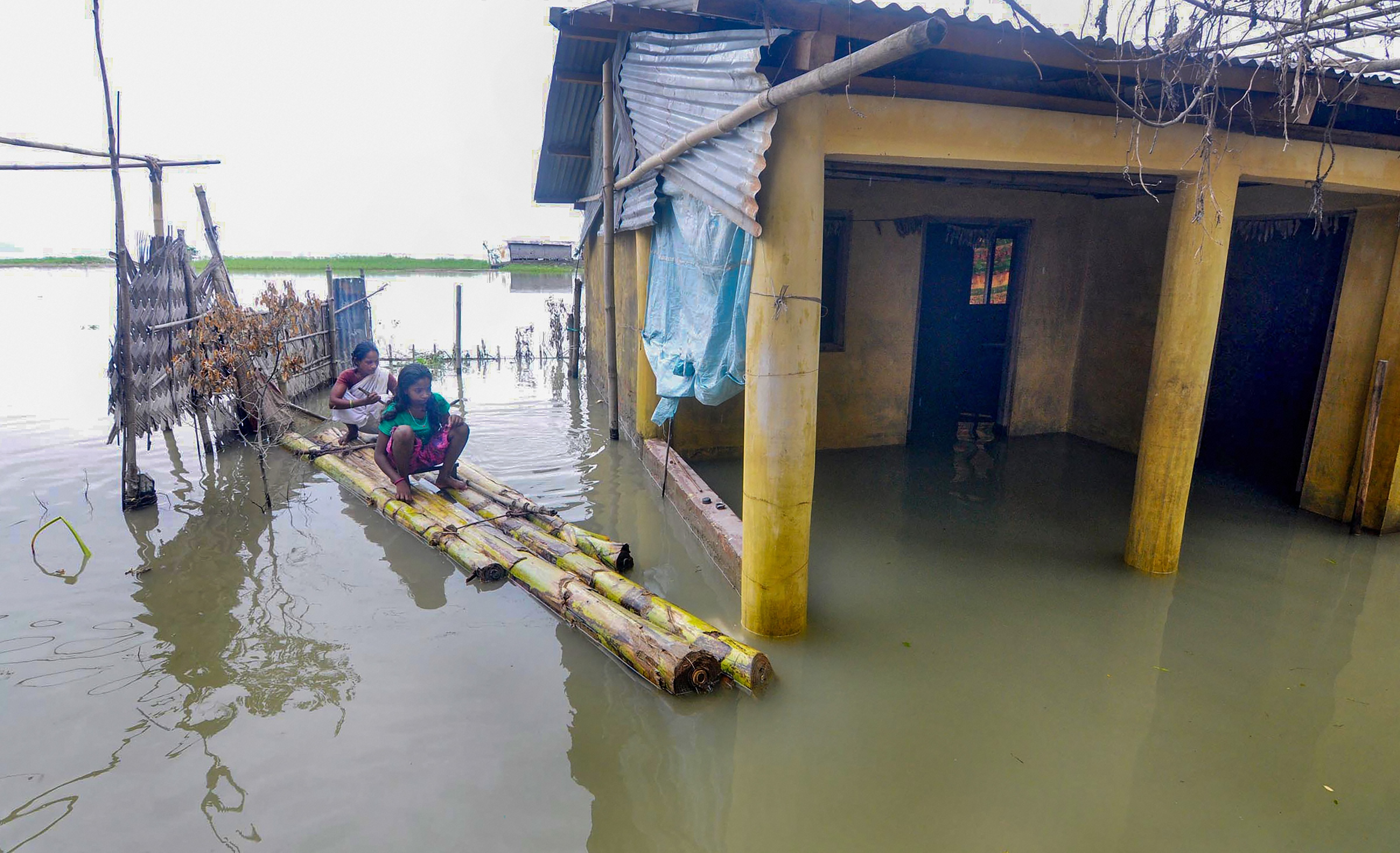 Kamrup: Flood affected villagers use a banana raft to move at Chandrapur in Kamrup district of Assam, Tuesday, July 21, 2020. (PTI Photo) (PTI21-07-2020_000053B)