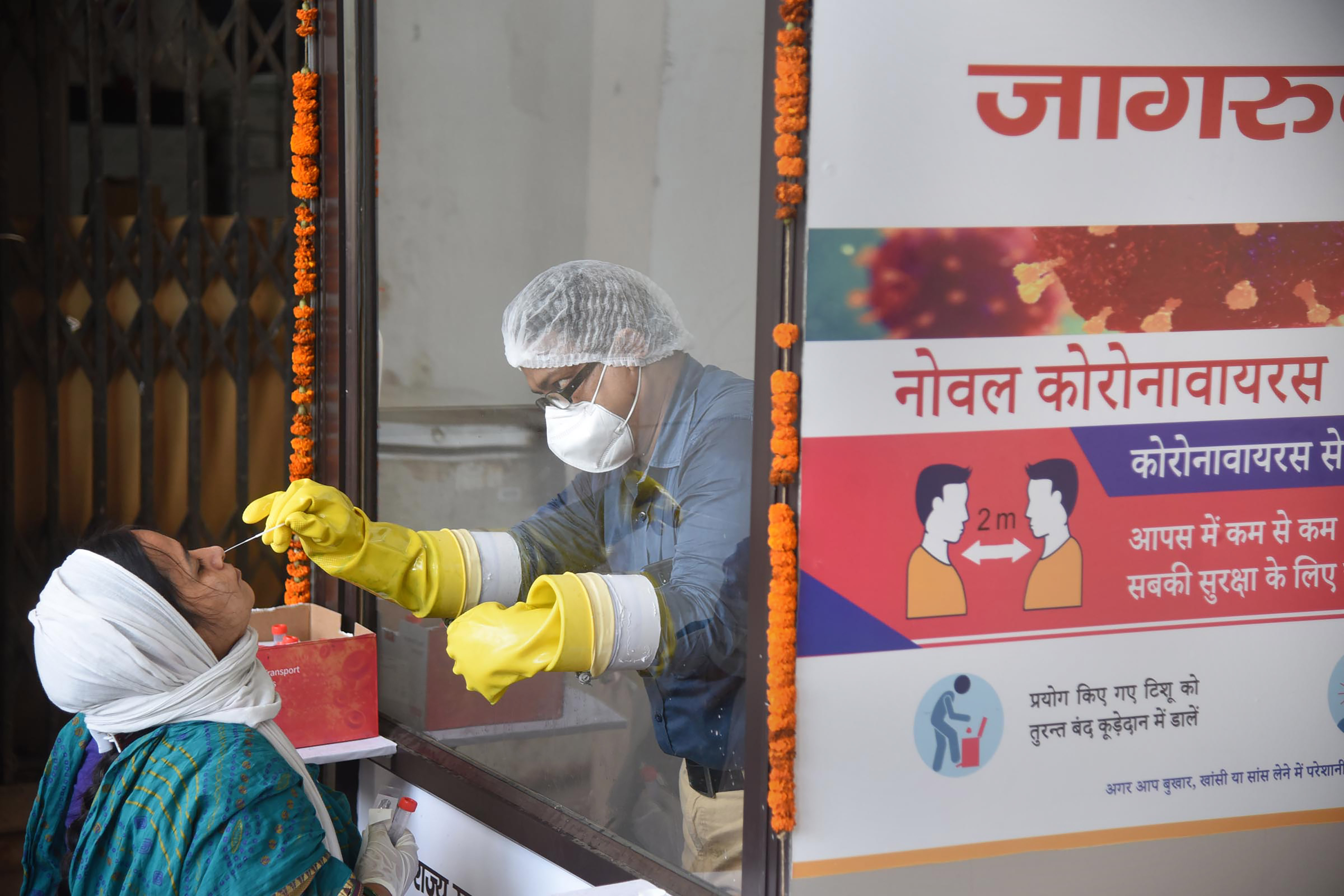 Patna: A medic collects a sample from a woman for COVID-19 test at a collection centre, during the total lockdown, in Patna, Friday, July 17, 2020. (PTI Photo)(PTI17-07-2020_000109B)