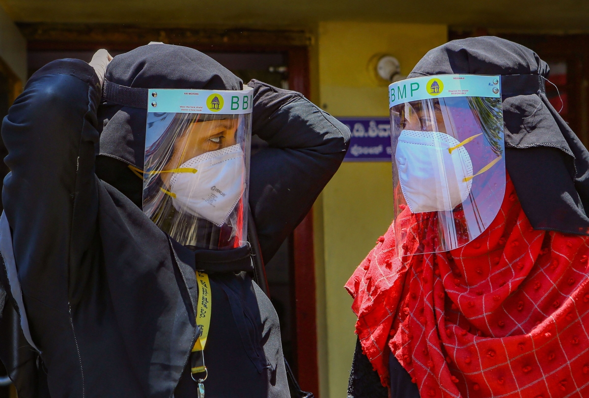 BBMP health workers adjust their visa shields before entering the areas of Padarayanapura in Chamarajapet during ongoing COVID-19 lockdown, in Bengaluru. (PTI)