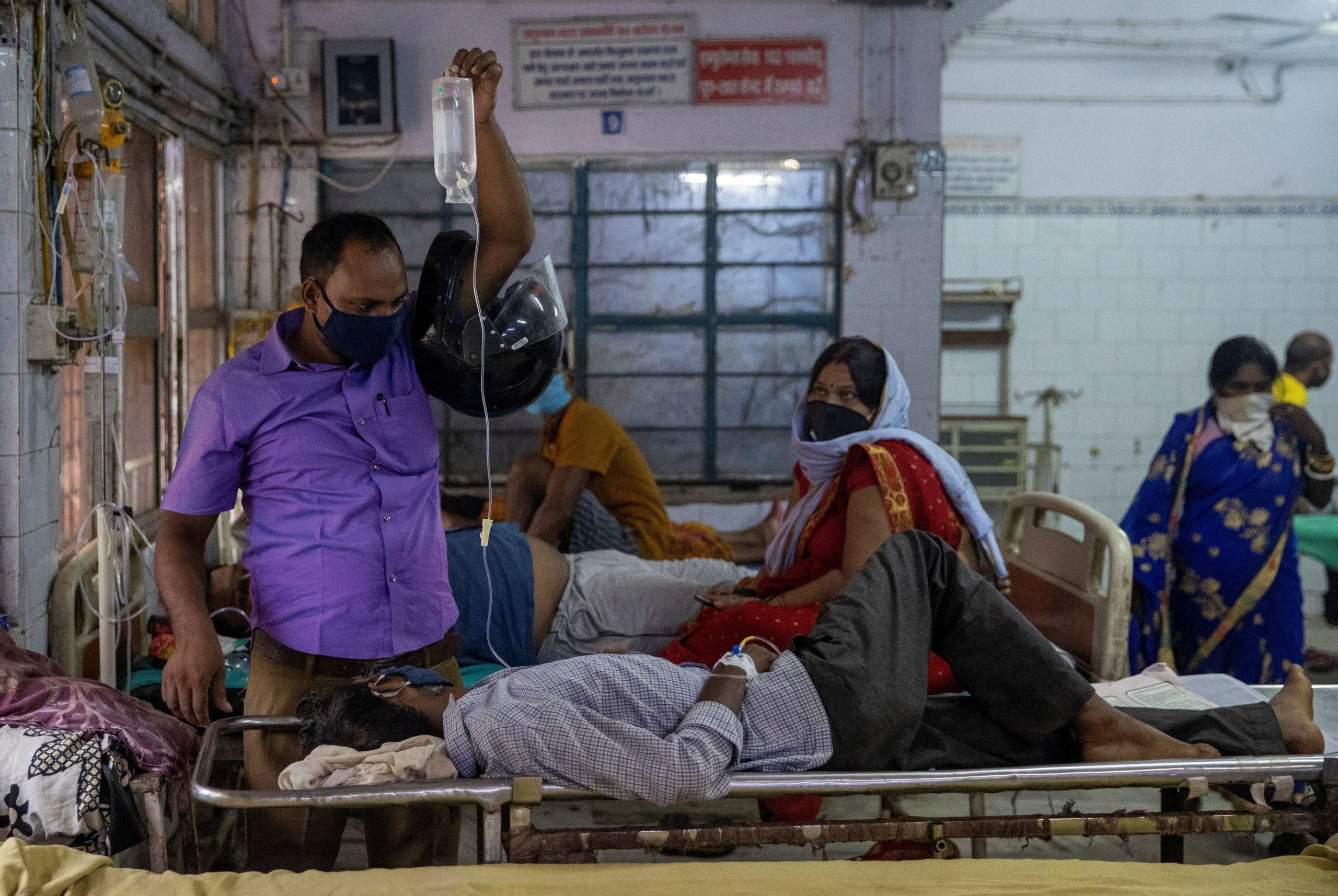 A man holds up an intravenous (IV) drip being used to treat his relative as they wait for him to be transferred to a hospital bed in the emergency ward of Jawahar Lal Nehru Medical College and Hospital, during the coronavirus disease (COVID-19) outbreak, in Bhagalpur, Bihar, India, July 28, 2020. REUTERS/Danish Siddiqui