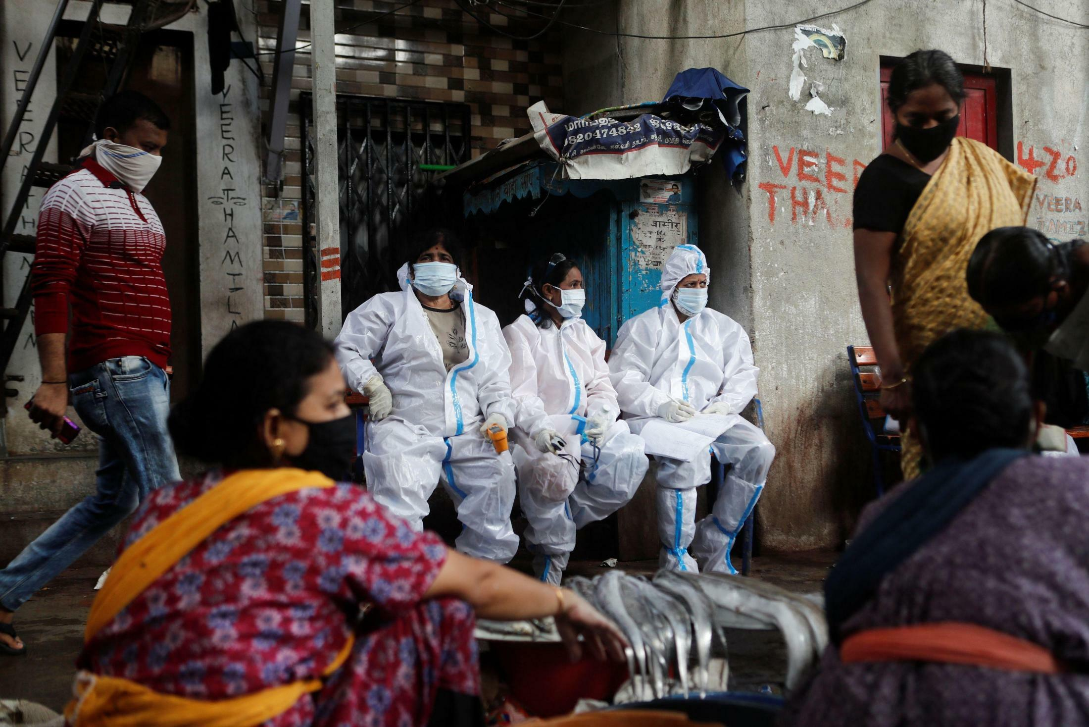 Health workers in personal protective equipment rest during a check up campaign for the coronavirus disease (COVID-19) at a slum area in Mumbai, India, August 3, 2020. REUTERS/Francis MascarenhasREUTERS