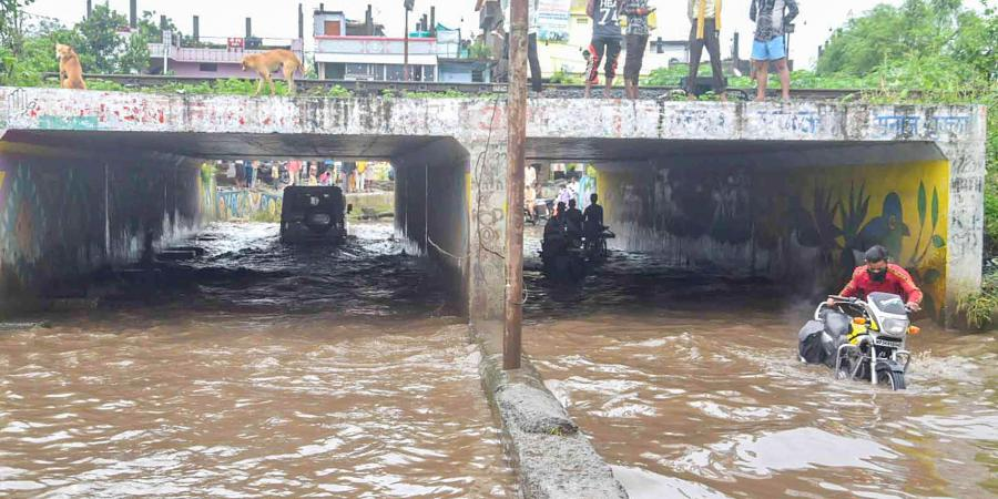Commuters move through a waterlogged underpass after heavy rainfall in Bhopal Saturday Aug 29 2020. (Photo | PTI)