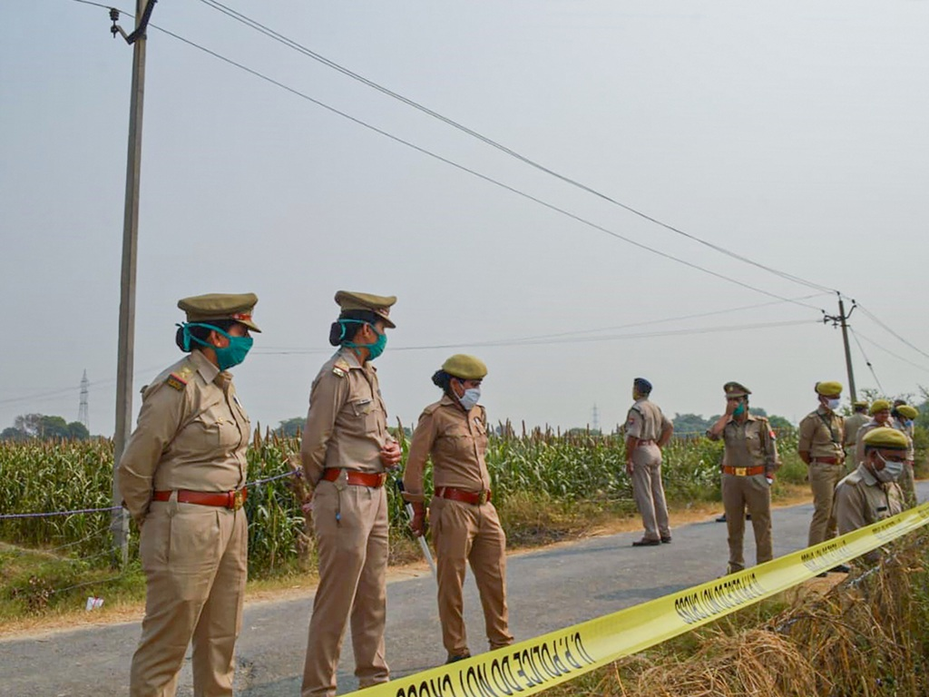 Hathras: Police personnel stand guard as CBI officials (unseen) investigate the case of a 19-year-old Dalit woman who died after being allegedly gang-raped, in Hathras, Tuesday, Oct. 13, 2020. (PTI Photo)(PTI13-10-2020 000190B)