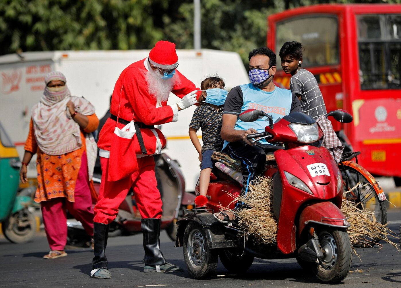 A man wearing a Santa Claus costume distributes free masks on an intersection, amidst the spread of the coronavirus disease (COVID-19), in Ahmedabad, India, December 18, 2020. REUTERS/Amit Dave