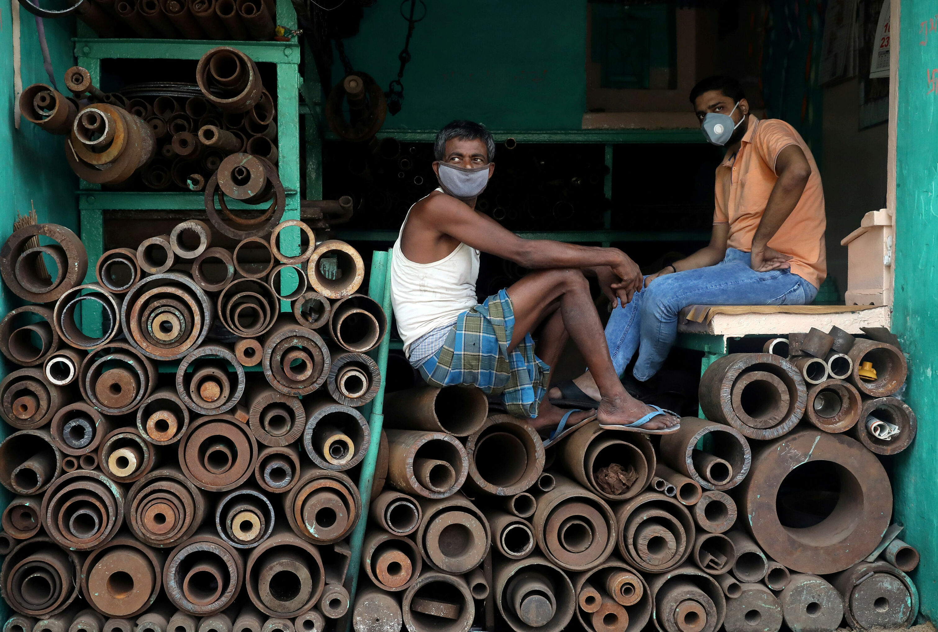Workers wearing protective face masks sit inside a shop selling iron pipes at a wholesale iron market, after authorities eased lockdown restrictions that were imposed to slow the spread of the coronavirus disease (COVID-19), in Kolkata, India, June 15, 2020. Credit: Reuters