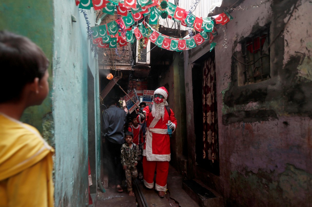 A man wearing a Santa Claus costume sanitizes the entrance of a house inside a slum, amidst the spread of the coronavirus disease (COVID-19), in Mumbai, India, December 19, 2020. (Photo by Francis Mascarenhas/Reuters)