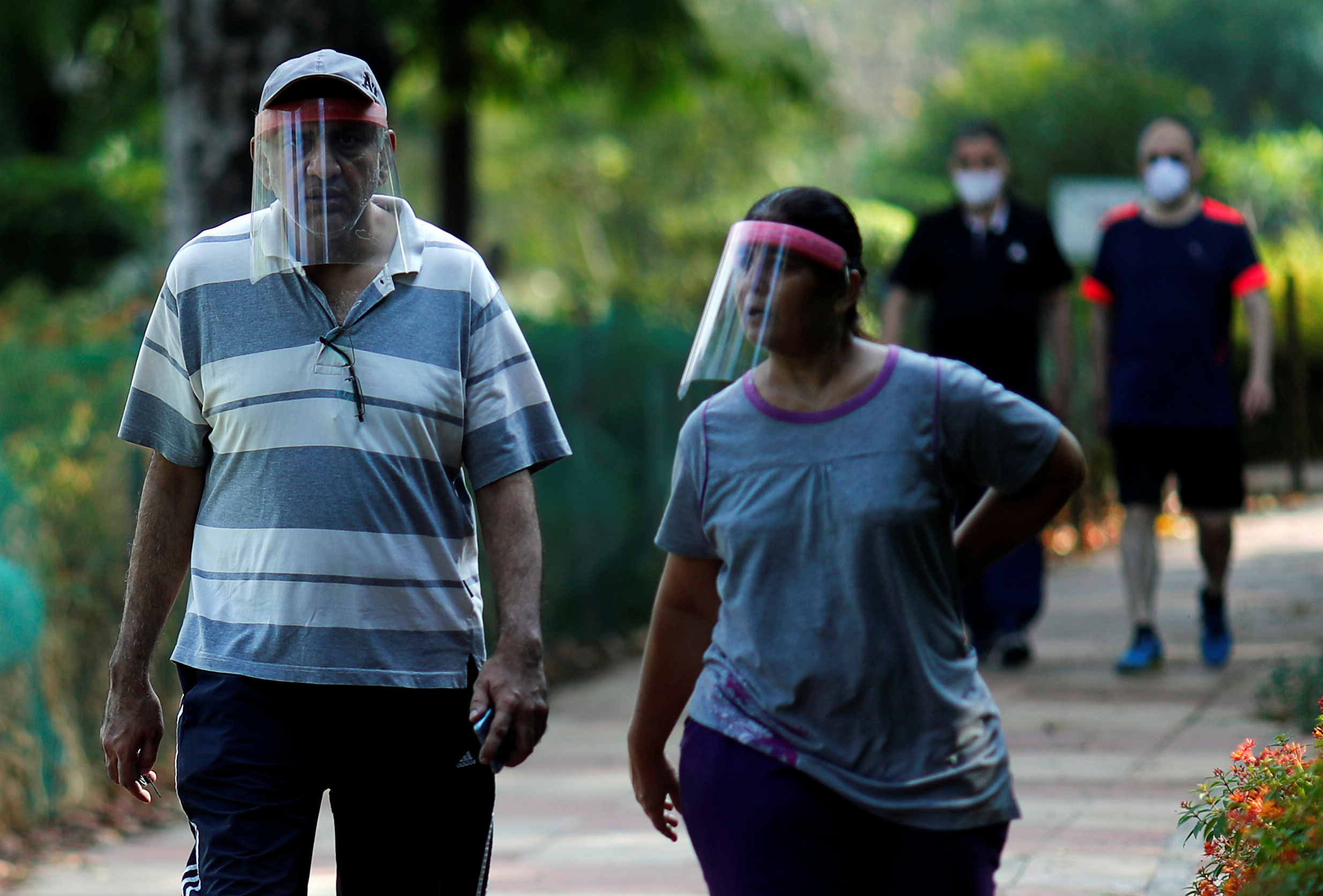 FILE PHOTO: People wearing protective face shields walk inside a park after few restrictions were lifted, during an extended nationwide lockdown to slow the spread of the coronavirus disease (COVID-19), in New Delhi, India, May 31, 2020. REUTERS/Adnan Abidi