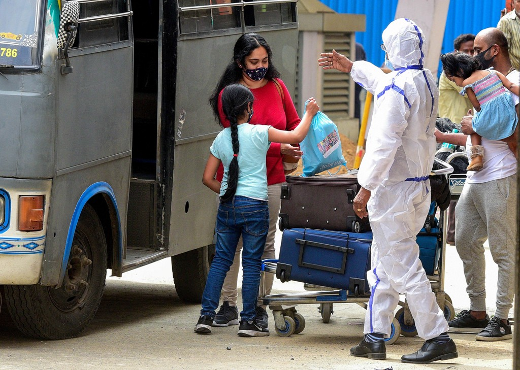 Chennai: A health worker guides passengers to a quarantine centre on their arrival from the United Kingdom, at the Chennai International Airpor, in Chennai, Tuesday, Dec. 22, 2020. Indian government has temporarily suspended all passengers flights from the United Kingdom in the wake the new COVID-19 strain found in the country. (PTI Photo) (PTI22-12-2020 000149B)