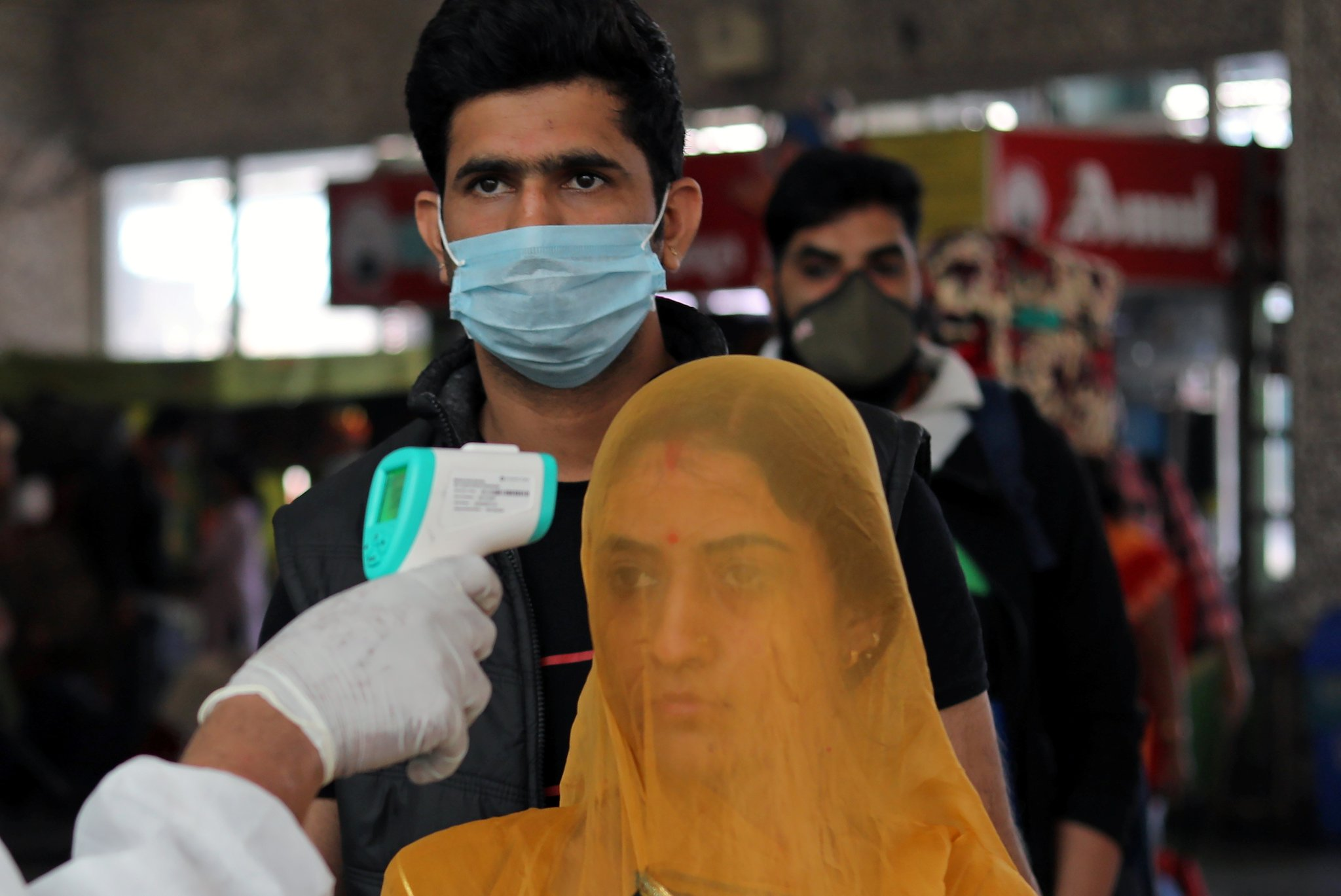 A health worker in personal protective equipment (PPE) checks the temperature of passengers amid the spread of the coronavirus disease (COVID-19), at a railway station in Mumbai, India, December 19, 2020. REUTERS/Francis Mascarenhas