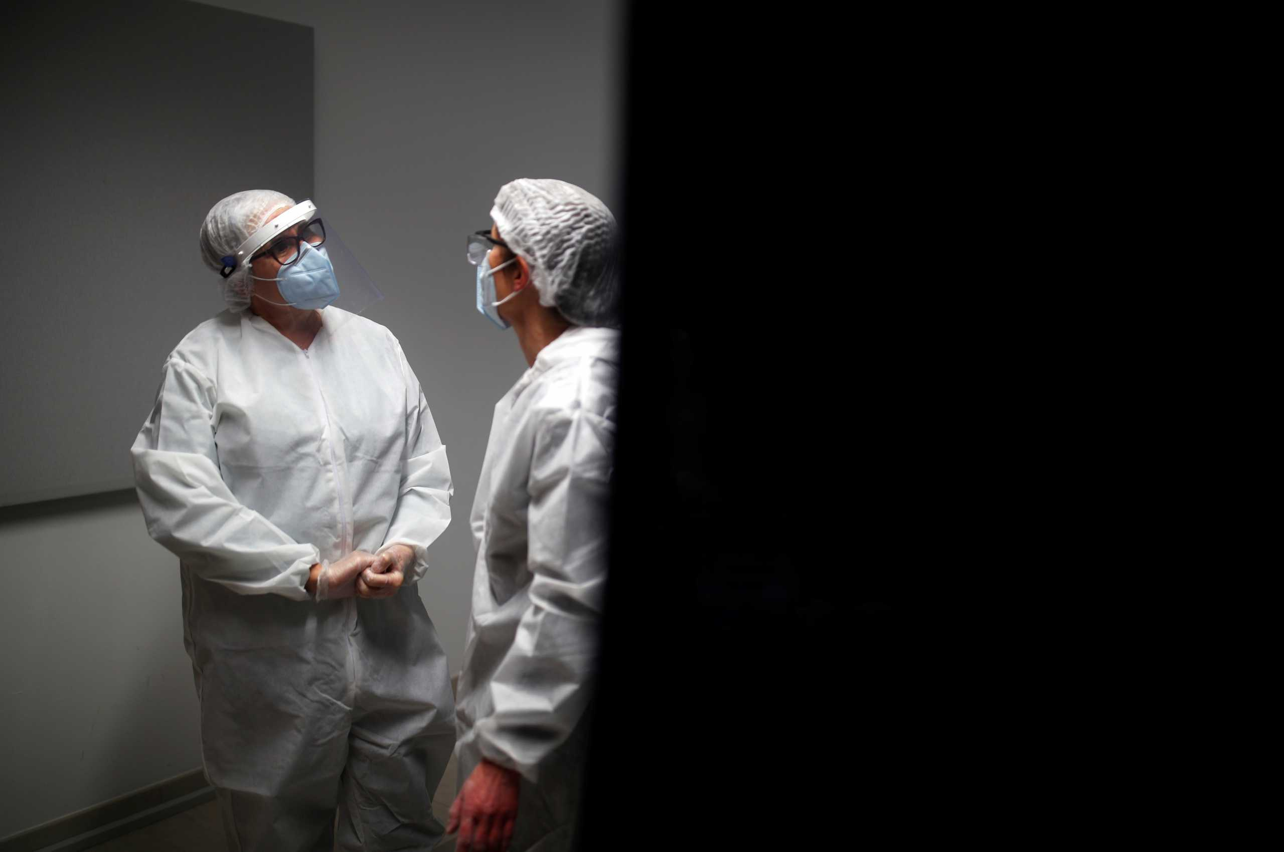 Medical workers, wearing protective suits and face masks, talk as they work at a coronavirus disease (COVID-19) testing centre in Le Bignon, France, December 22, 2020. REUTERS/Stephane Mahe/File Photo