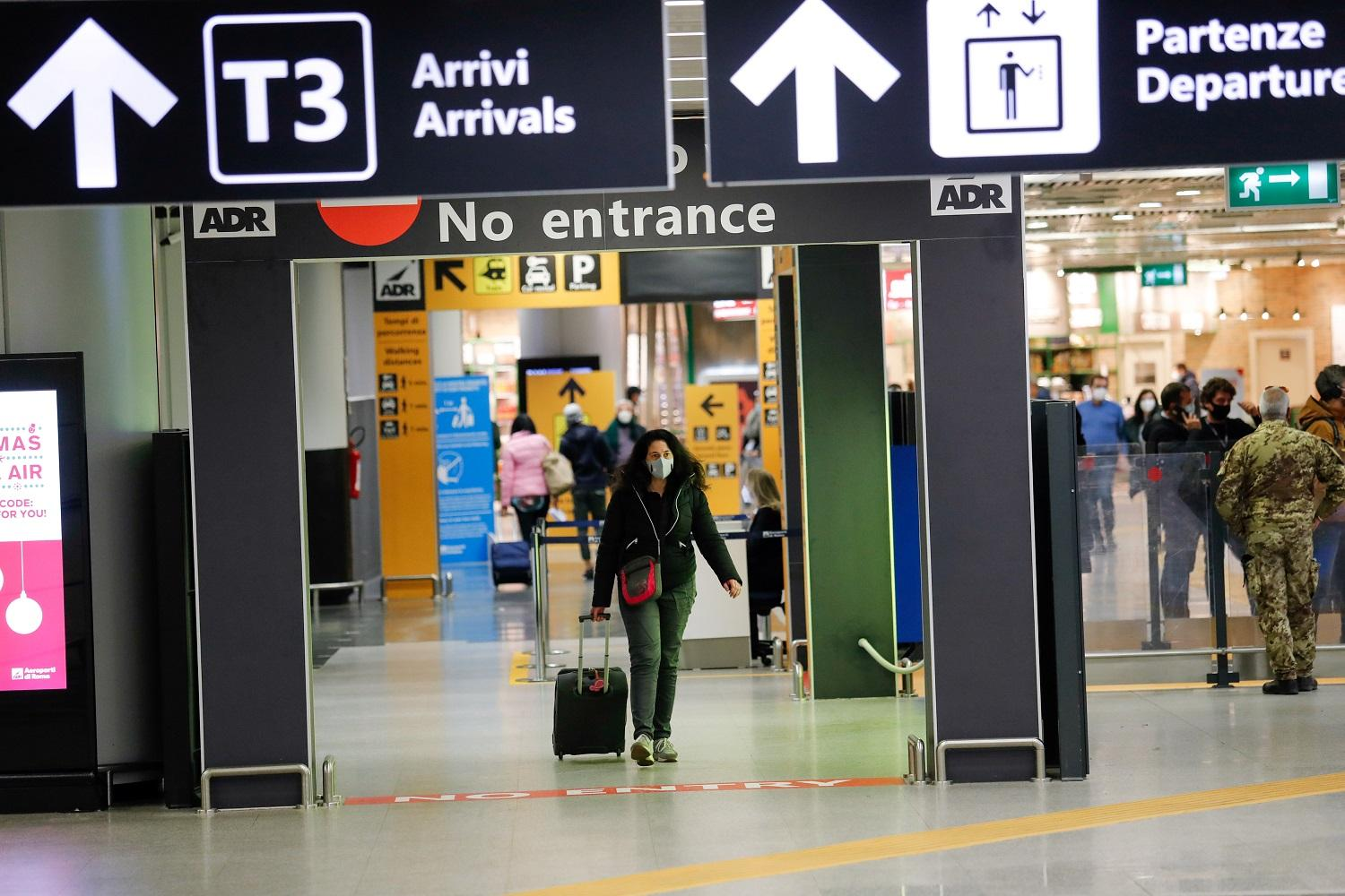A passenger walks at Rome airport after Italy announced all flights to and from the UK will be suspended [Remo Casilli/Reuters]