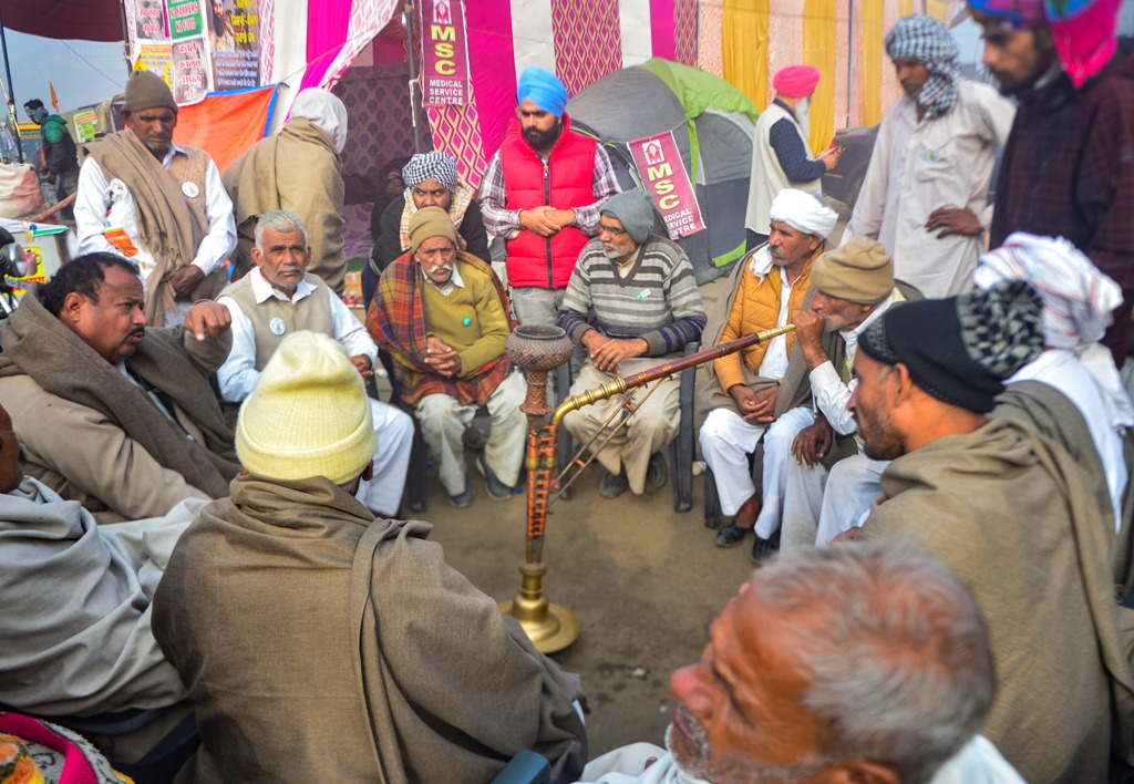New Delhi: A farmer smokes hookah as others interact at Singhu border during their ongoing protest against the Centres farm reform laws, in New Delhi, Tuesday, Dec. 8, 2020. The farmers have called for a nationwide strike demanding repeal of the agri laws. (PTI Photo/Ravi Choudhary)(PTI08-12-2020 000040B)