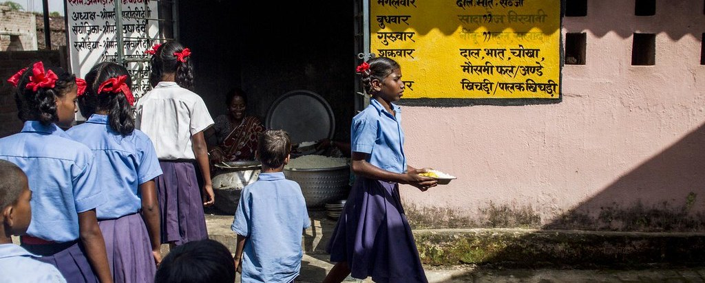 Students stand in a queue for mid-day meals at a government middle school in a village in Jharkhand. Photo: Unicef India/Flickr, CC BY 2.0