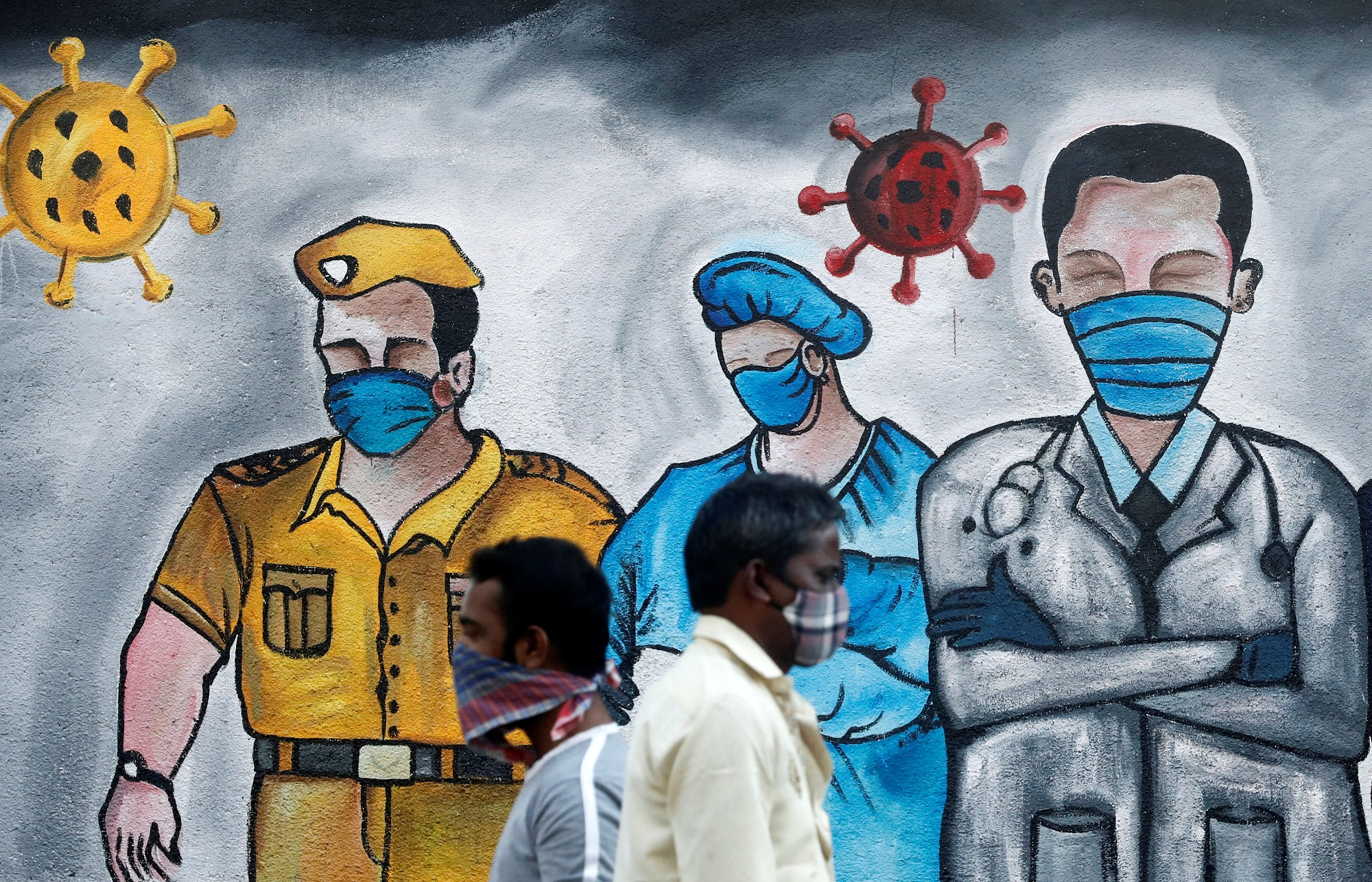 Men walk past a mural of frontline workers amid the spread of the coronavirus disease (COVID-19), in Mumbai on December 21, 2020. (REUTERS)