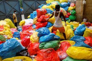 दिल्ली के एक अस्पताल से मेडिकल कचरा निकालता एक कर्मचारी. (फोटो: (फोटो: रॉयटर्स/अदनान आबिदी)