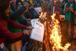 New Delhi: Farmers burn copies of the new farm laws as they celebrate Lohri festival during their ongoing protest against the central government, at Singhu border in New Delhi, Wednesday, Jan. 13, 2021. (PTI Photo/Manvender Vashist)(PTI01 13 2021 000275B)