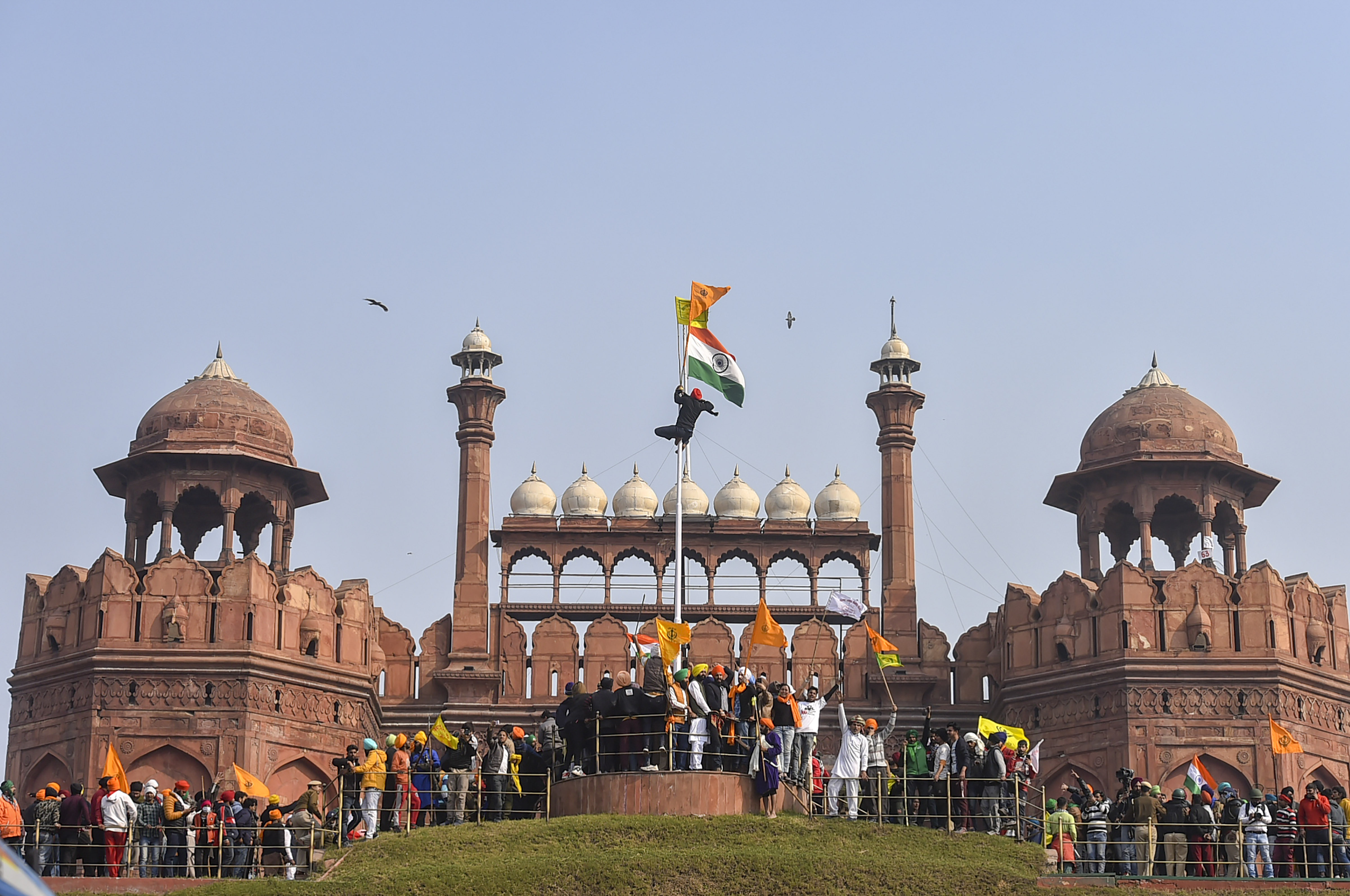 New Delhi: Farmers hoist flags at the Red Fort during the 'tractor rally' amid the 72nd Republic Day celebrations, in New Delhi, Tuesday, Jan. 26,  2021. (PTI Photo/Arun Sharma)(PTI01_26_2021_000385B)