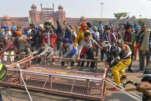 गणतंत्र दिवस के दिन नई दिल्ली के लाल किले में किसान पुलिस द्वारा लगाए बैरिकेड्स को हटाते हुए. (फोटो: पीटीआई)