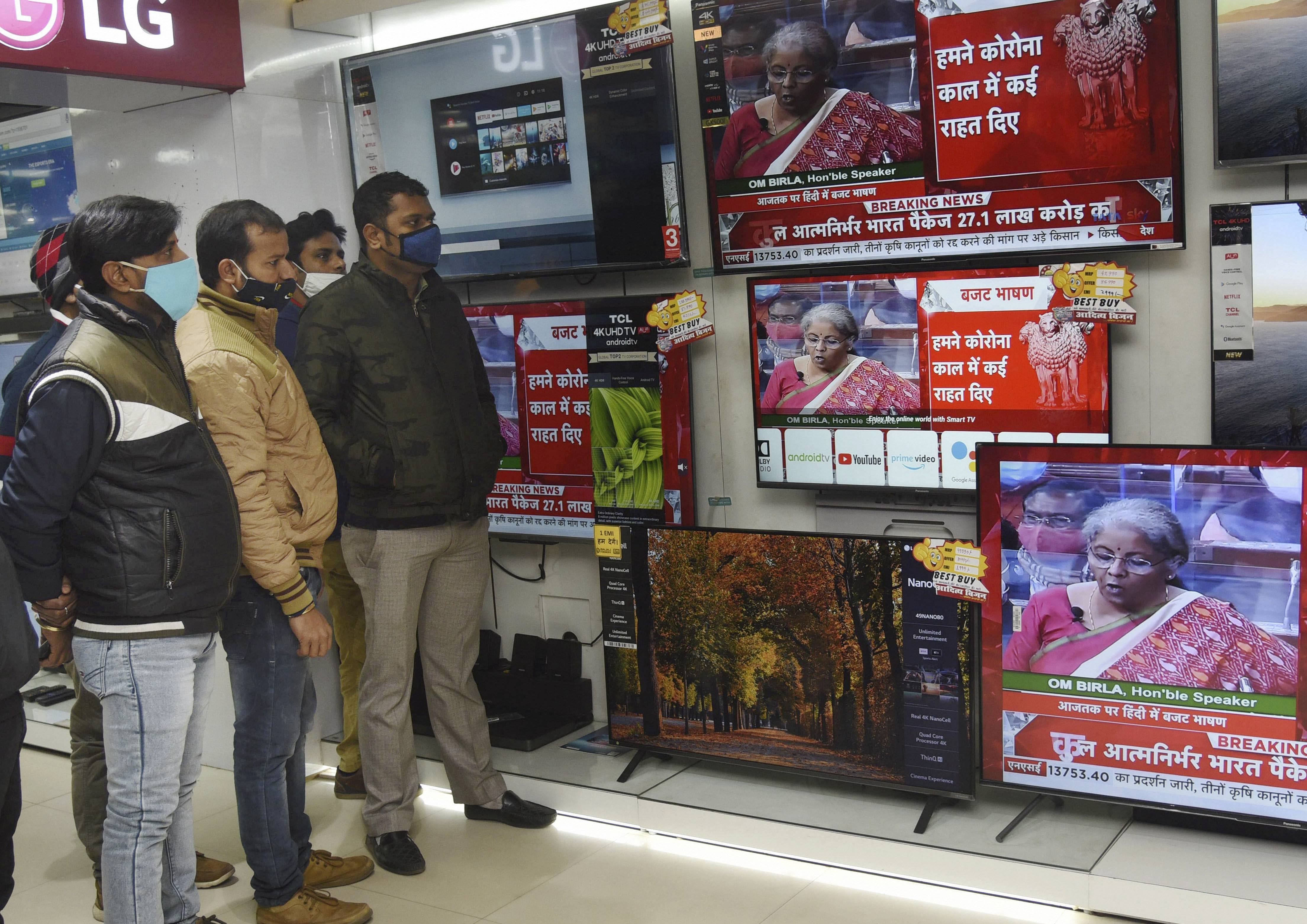 Patna: People watch Finance Minister Nirmala Sitharaman present the Union Budget 2021-21 on television sets, during the Budget Session of Parliament, at an electronics store in Patna, Monday, Feb, 1, 2021. (PTI Photo)(PTI02_01_2021_000061B)