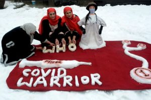 Two sisters Qurat-ul-Ain Zohra and Aiman Zohra along with their mother give a final touch to a snow sculpture to honour health workers and their fight against COVID-19, after a heavy snowfall, outside their residence in Srinagar, Jan. 10, 2021. | PTI