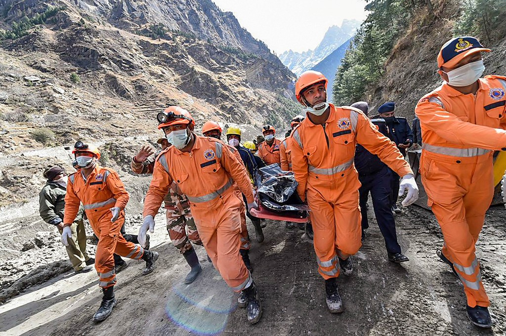 Chamoli: NDRF personnel carry the body of a victim who died in the massive floods caused after a glacier broke off in Joshimath in the Dhauli Ganga river, near Raini village in Chamoli district of Uttarakhand, Tuesday, Feb. 9, 2021. (PTI Photo/Arun Sharma)(PTI02 09 2021 000108B)