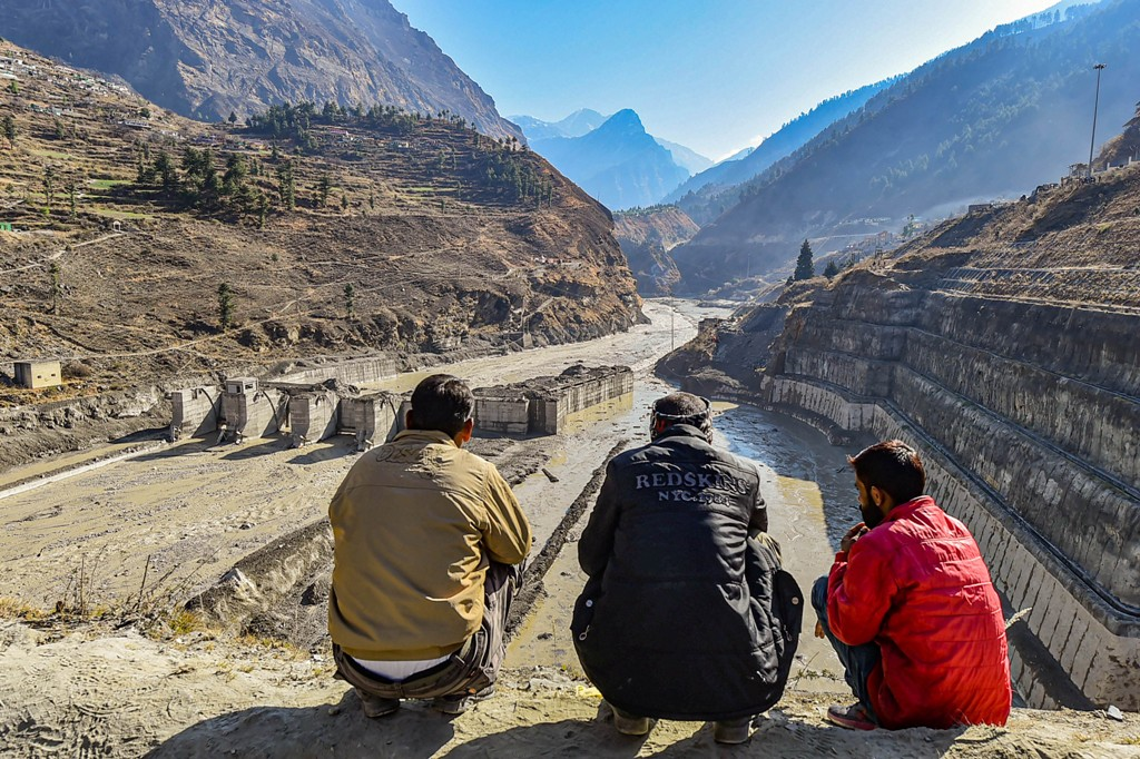 Chamoli: Villagers watch the rescue operations carried at Tapovan barrage, following the Sundays glacier burst in Joshimath causing a massive flood in the Dhauli Ganga river, in Chamoli district of Uttarakhand, Wednesday, Feb. 10, 2021. (PTI Photo/Arun Sharma) (PTI02 10 2021 000065B)