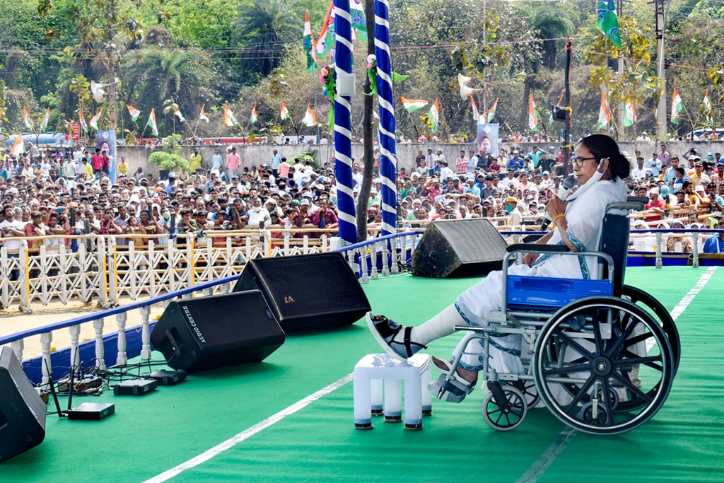 Bankura: West Bengal CM and TMC supremo Mamata Banerjee, sitting on a wheel-chair, addresses an election campaign rally ahead of state assembly polls, in Bankura, Tuesday, March 16, 2021. (PTI Photo)(PTI03 16 2021 000071B)