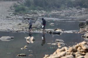 मिजोरम के सीमाई जिले चम्पाई के एक गांव में टीओ नदी पार करते लोग. (फोटो: रॉयटर्स)