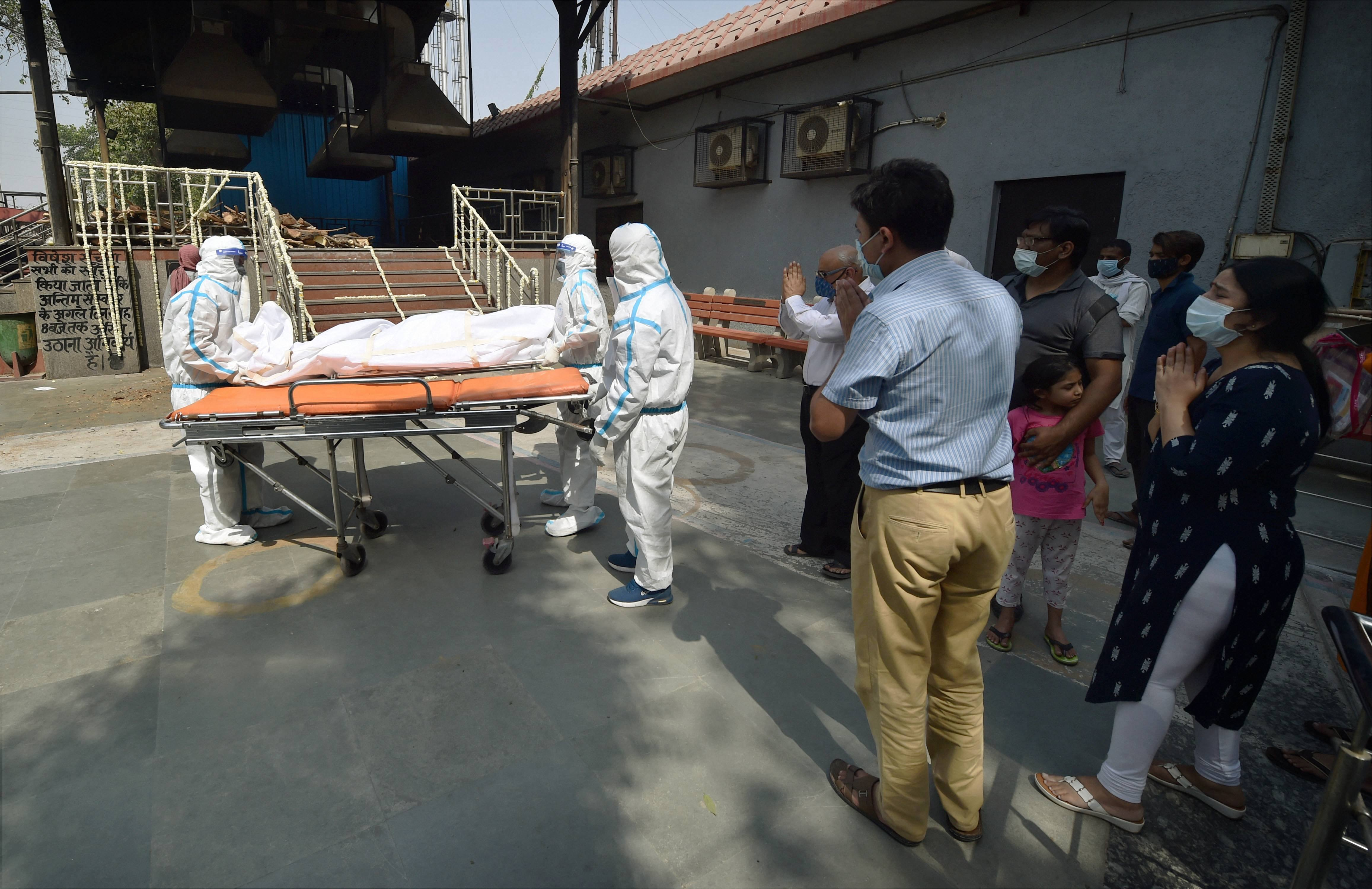 **EDS: RPT CORRECTS DETAILS** New Delhi: Health workers take the mortal remains of a person, who died of COVID-19, as family members offer prayers at Nigam Bodh Ghat crematorium, in New Delhi,Sunday, April 11, 2021. (PTI Photo/Manvender Vashist) (PTI04_11_2021_000117B)