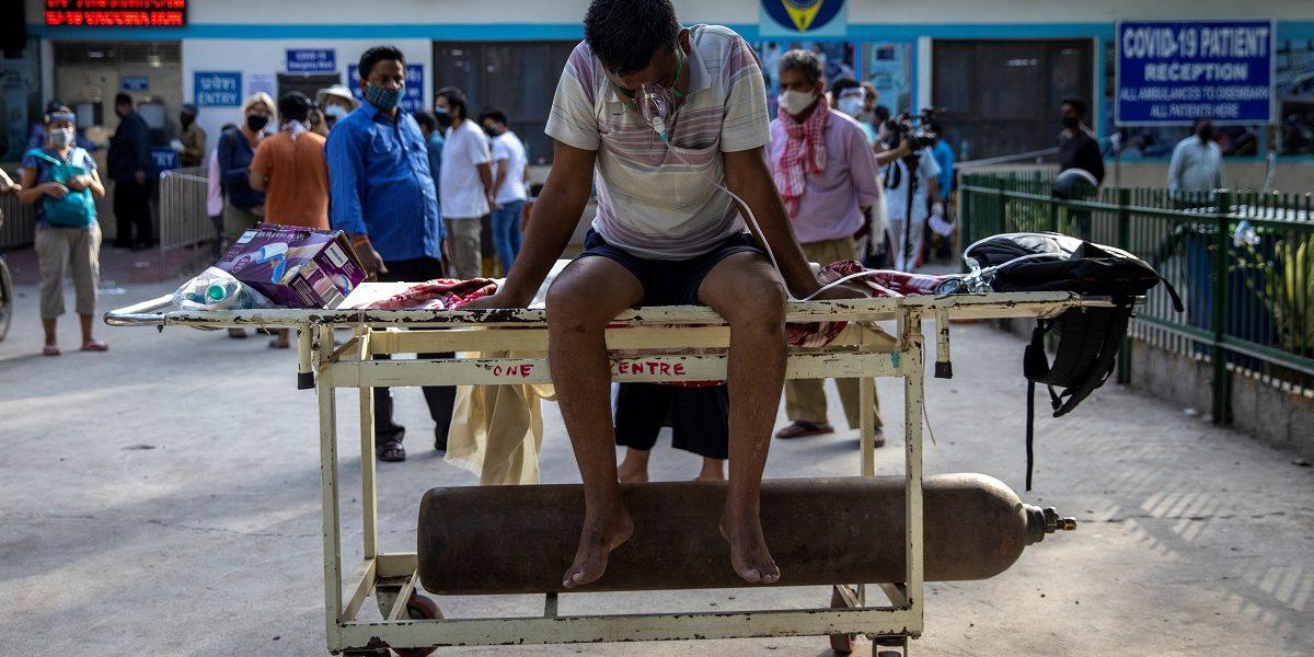 जीटीबी अस्पताल में भर्ती होने का इंतज़ार करता एक कोविड संक्रमित शख़्स. (फोटो: रॉयटर्स)