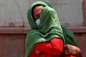 नई दिल्ली के एक कोविड अस्पताल में अपने पिता की मौत से दुखी उनकी बेटी. (फोटो: रॉयटर्स)