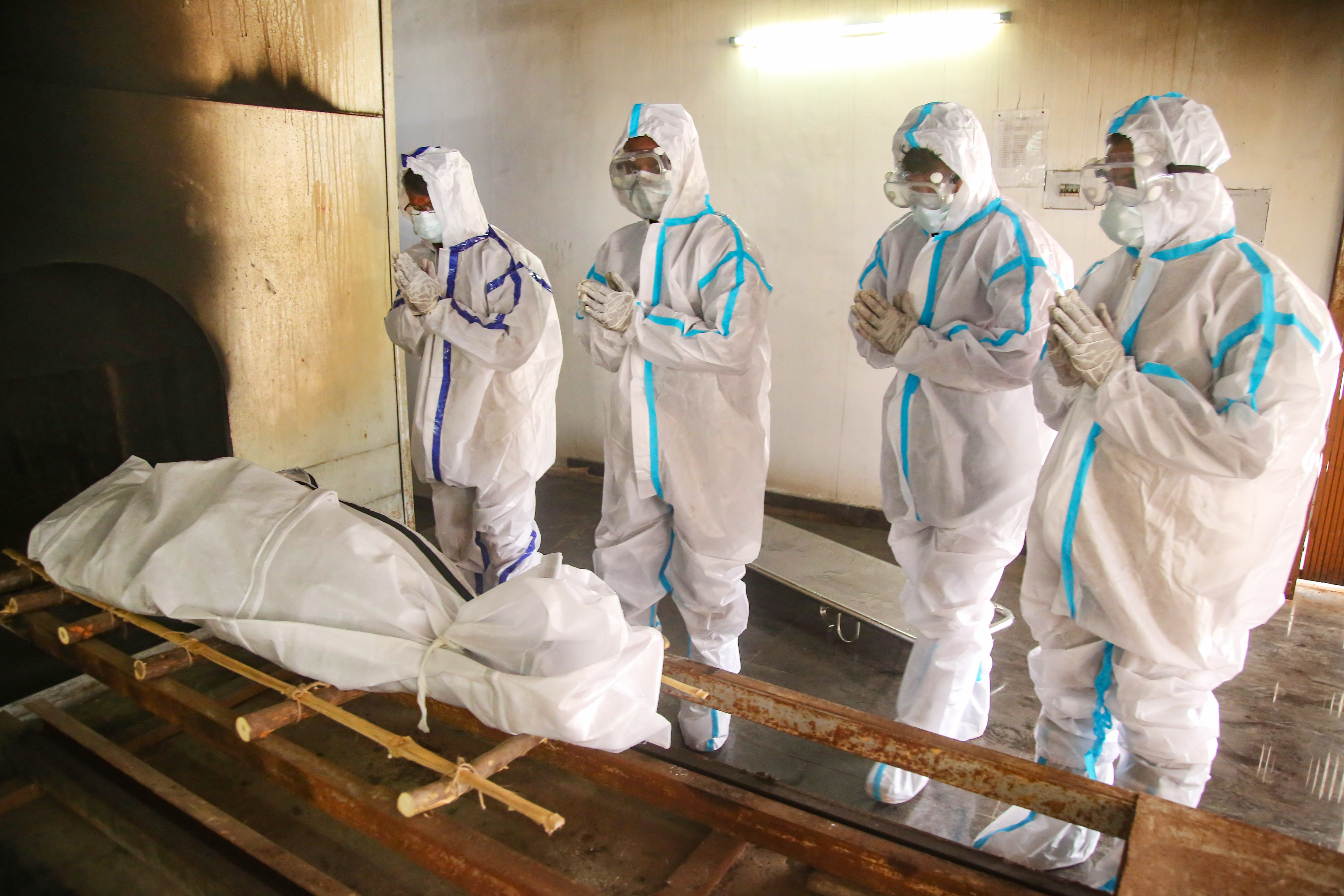 Kanyakumari: Relatives and family members wearing PPE perform prayers before cremating the body of a person who died of COVID-19, amid the ongoing surge in coronavirus cases, at Nagercoil in Kanyakumari district, Monday, April 12, 2021. (PTI Photo)(PTI04_12_2021_000058B)