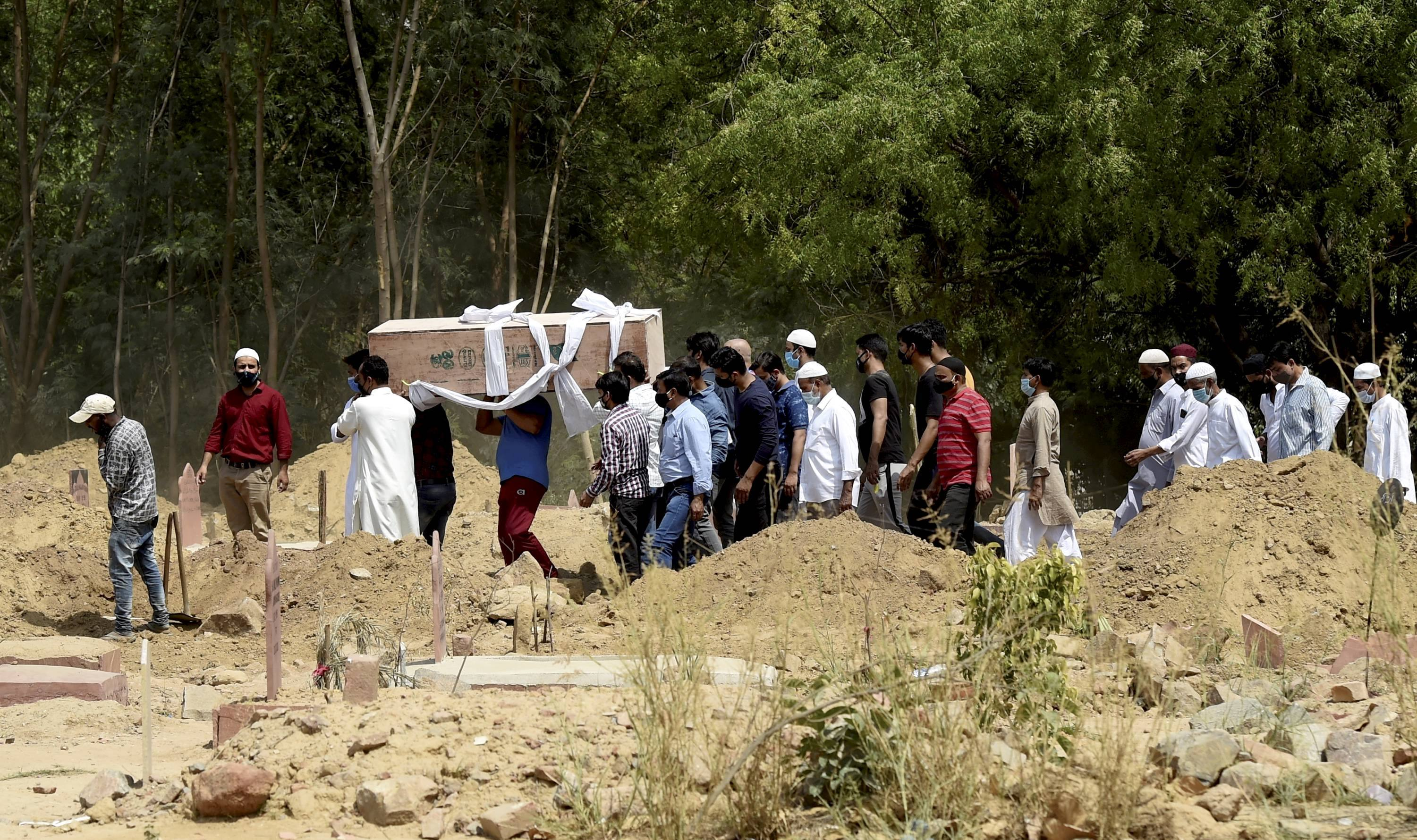 New Delhi: Family members and relatives perform burial of a person who succumbed to COVID-19, at a graveyard in New Delhi, Tuesday, April 13, 2021. (PTI Photo/Manvender Vashist)(PTI04_13_2021_000148B)