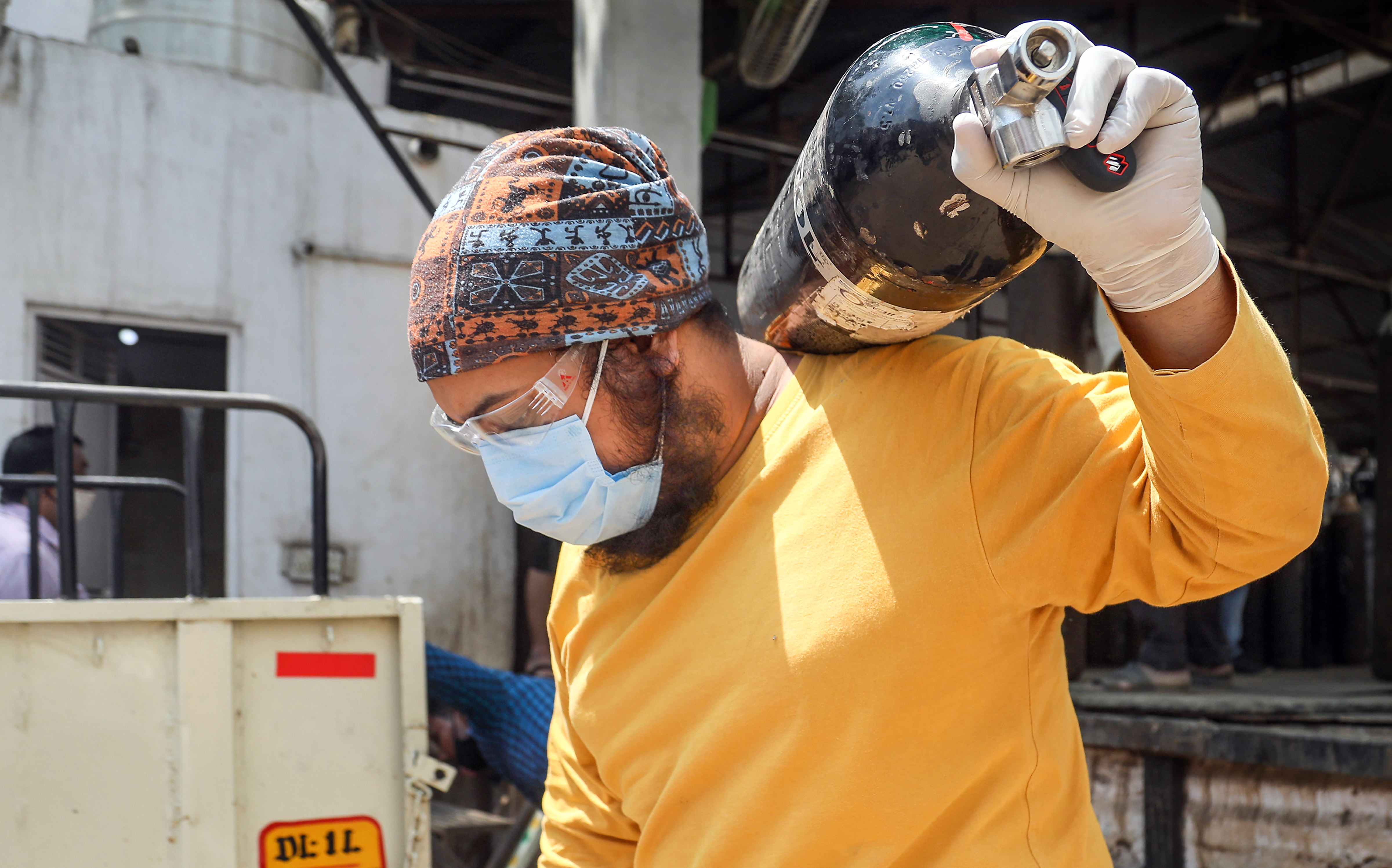 New Delhi: A relative of a COVID-19  patient carries empty oxygen cylinders for refilling, as coronavirus cases surge across the country, in New Delhi, Wednesday, April 21, 2021. (PTI Photo)(PTI04_21_2021_000111B)
