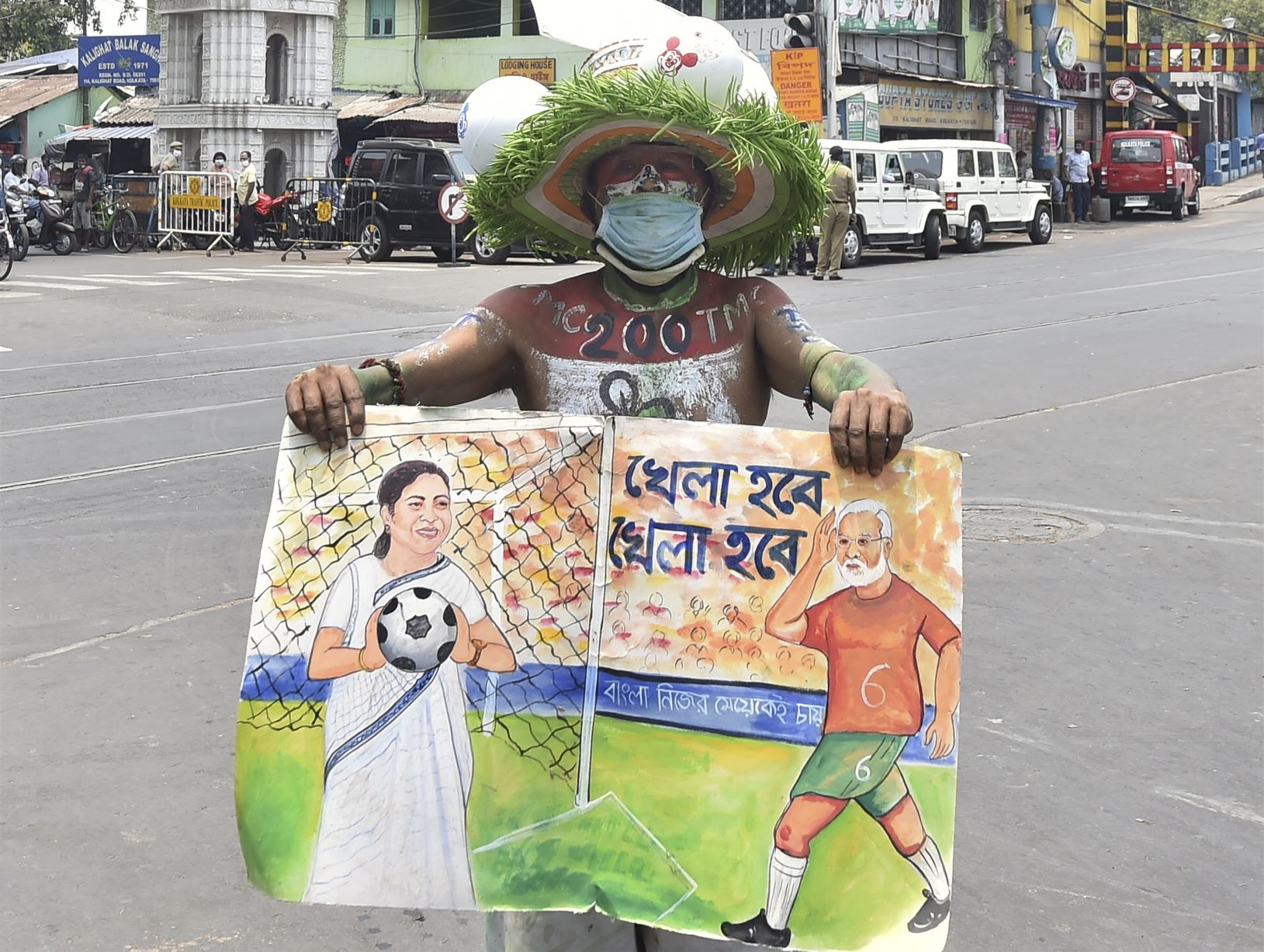 Kolkata: A TMC supporter holds a placard outside West Bengal Chief Minister Mamata Banerjees residence at Kalighat during the counting of West Bengal Assembly poll, as the state government observes a shutdown to combat the Covid-19 situation, no gathering and rallies are strictly prohibited in this situation in Kolkata, Sunday, May 2, 2021.(PTI Photo/Swapan Mahapatra)(PTI05 02 2021 000061B)