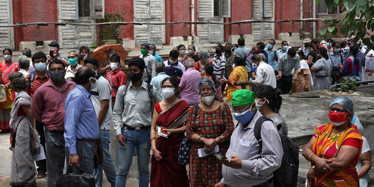 कोलकाता के एक टीकाकरण केंद्र पर खुराक लेने का इंतज़ार करते लोग. (फोटो: रॉयटर्स)