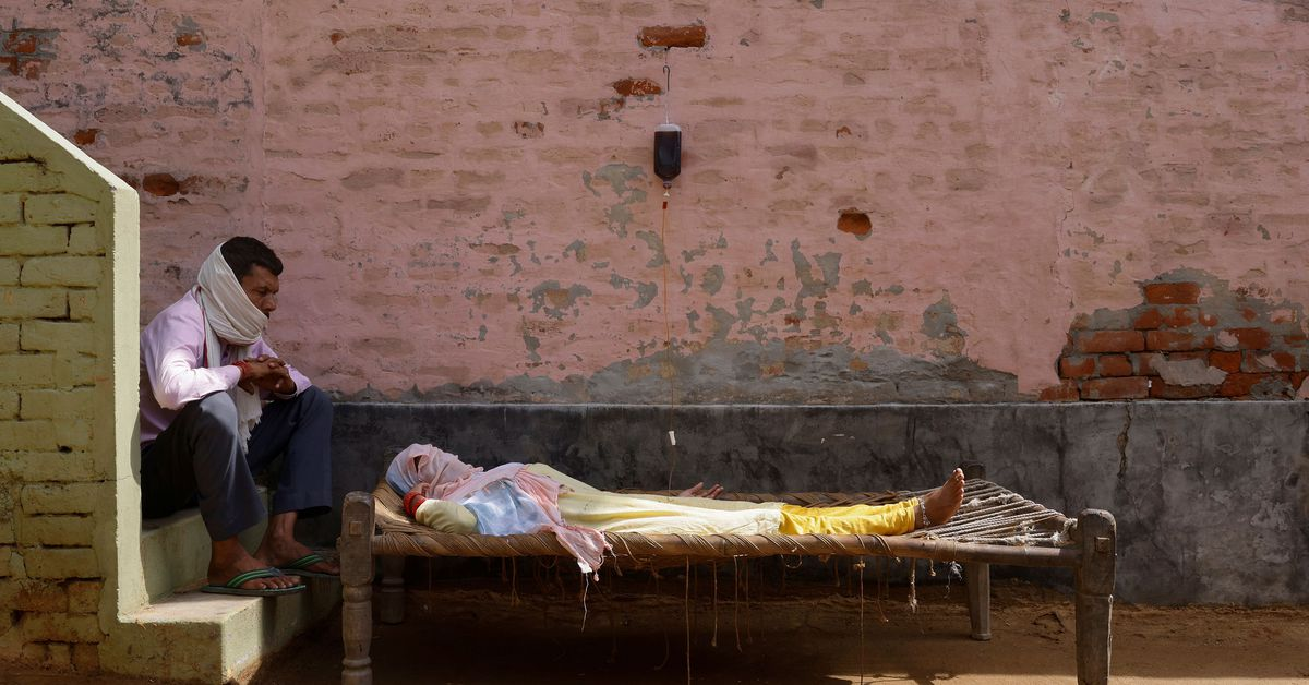 A man sits next to his wife, who is suffering from fever as she receives treatment at a clinic set up by a local villager, amidst the spread of the coronavirus disease (COVID-19), in Parsaul village in Greater Noida, in the northern state of Uttar Pradesh, India, May 22, 2021. REUTERS/Adnan Abidi