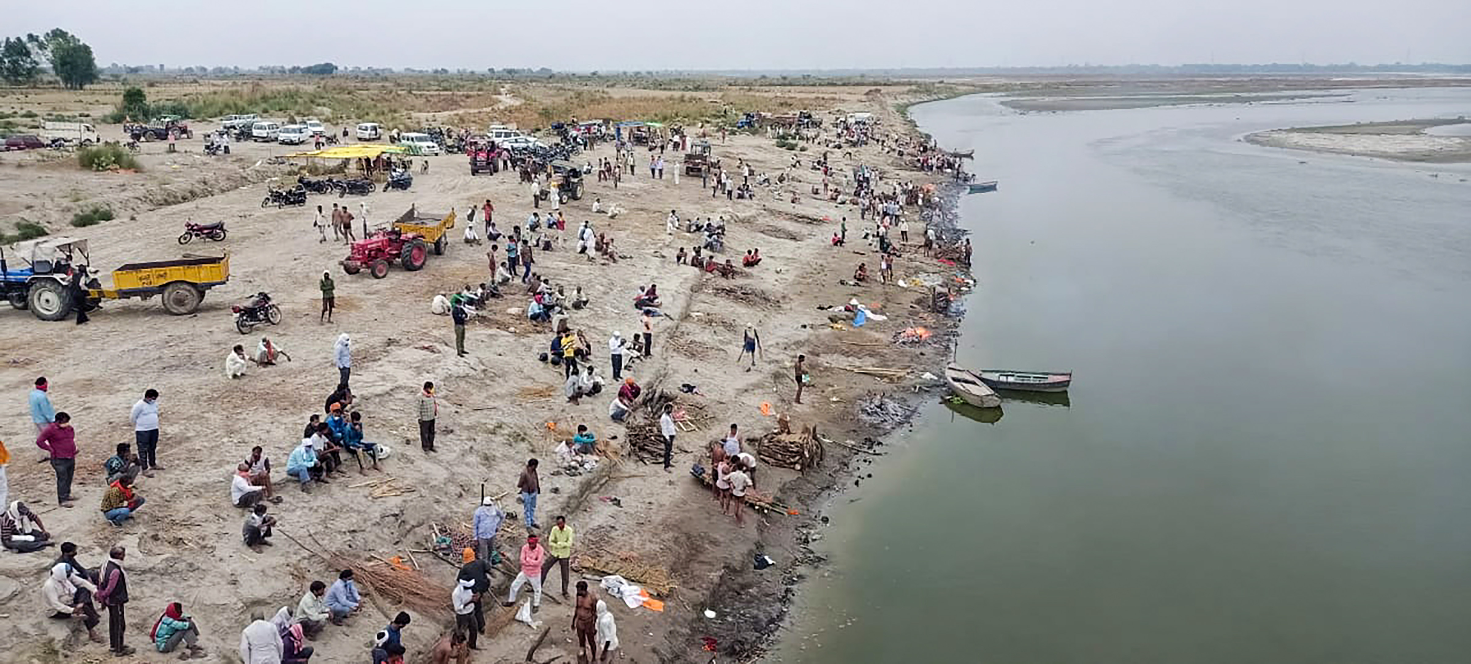 Unnao: Relatives and family wait to cremate on the banks of River Ganga, in Unnao, Thursday, May 13, 2021. (PTI Photo)(PTI05_13_2021_000100B)