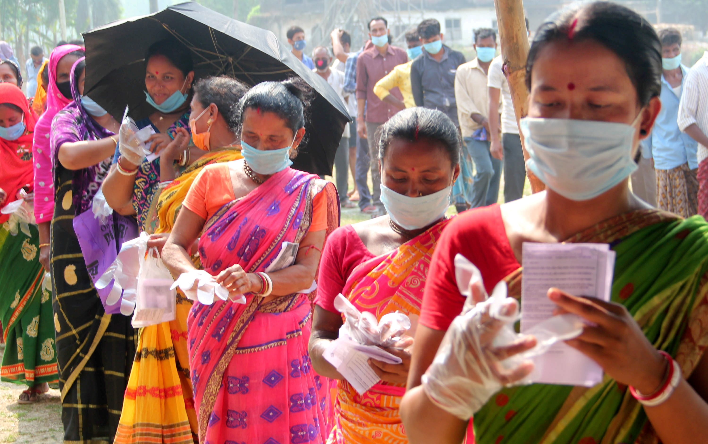 South Dinajpur: Voters wait in queues to cast votes at a polling station during the 7th phase of West Bengal Assembly elections at a village near Balurghat in South Dinajpur district on Monday, April 26, 2021.  (PTI Photo) (PTI04_26_2021_000067B)