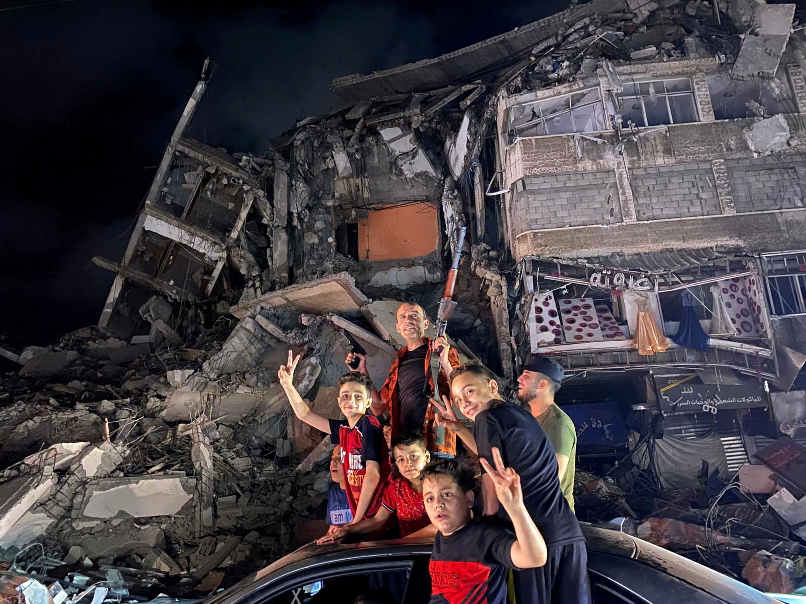 People gesture near the rubble of a damaged building as Palestinians celebrate in the streets following a ceasefire, in Gaza City May 21, 2021. REUTERS/Mohammed Salem
